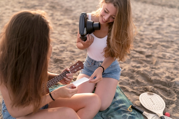 Amis assis sur la plage en regardant la photo polaroid