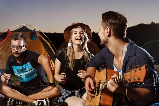 Amis assis près de feu de joie, souriant, jouant de la guitare camping grill guimauve.