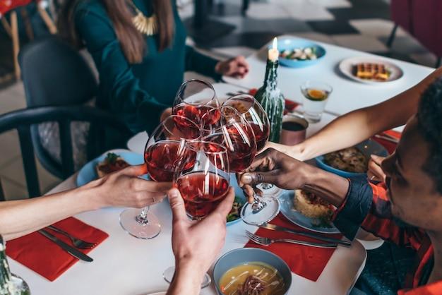Amis assis à une table buvant des verres à vin.