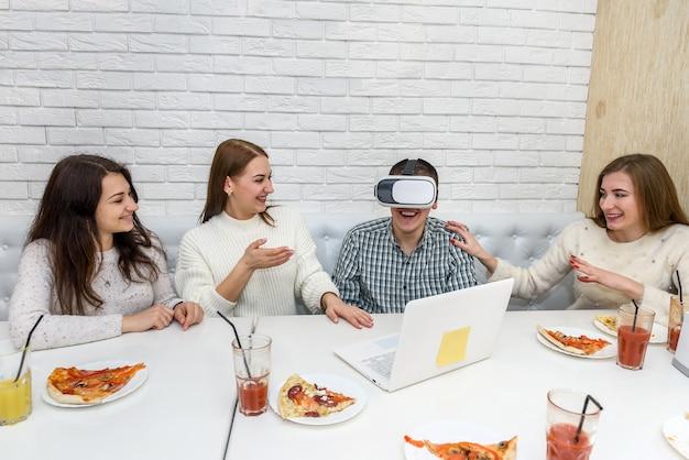 Amis au café manger de la pizza et essayer des lunettes virtuelles 3d