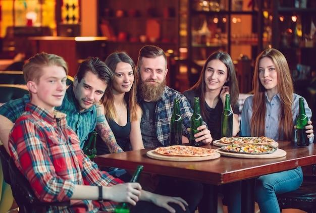 Amis, avoir des boissons et manger des pizzas dans un bar