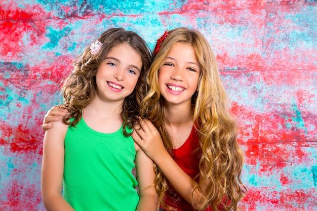 Amis beaux enfants filles câlin ensemble heureux souriant