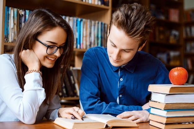 Amis à la bibliothèque assis à la table et à la recherche d'informations dans le livre