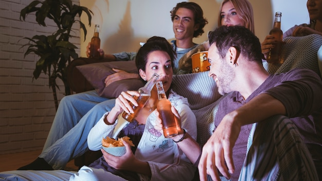 Amis avec de la bière ayant une soirée de cinéma