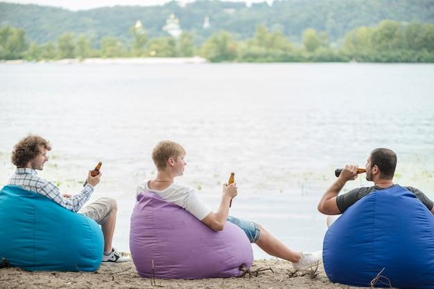 Amis avec de la bière se détendre près de l'eau