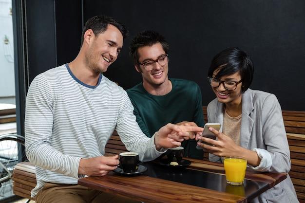 Amis, boire du café et du jus d'orange tout en regardant le smartphone