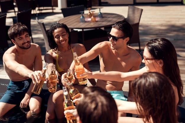 Amis avec des boissons alcoolisées au bord de la piscine