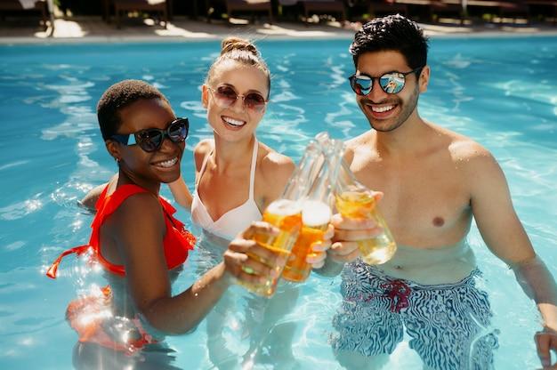 Les amis boivent des boissons dans la piscine, vue de dessus