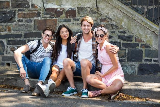 Amis branchés souriant à la caméra assis sur le trottoir