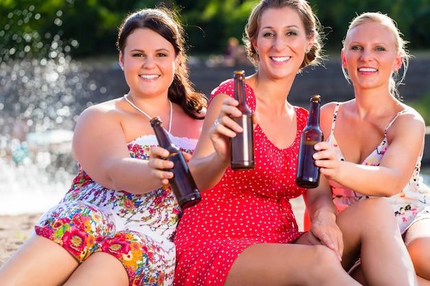 Amis, buvant de la bière à la plage de la rivière