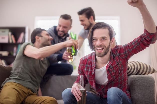 Amis buvant de la bière et regardant un match de football