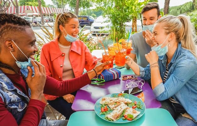Amis buvant un coktail et mangeant des tapas dans un bar-restaurant à l'extérieur les jours d'été avec un masque facial pour être protégés du coronavirus - des gens heureux applaudissant avec du spritz et s'amusant
