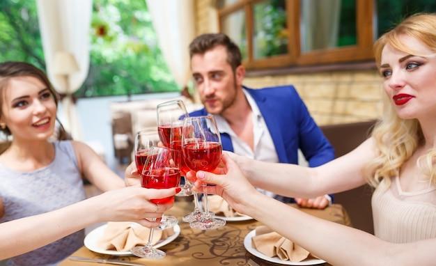 Amis buvant du vin sur la terrasse d'été.