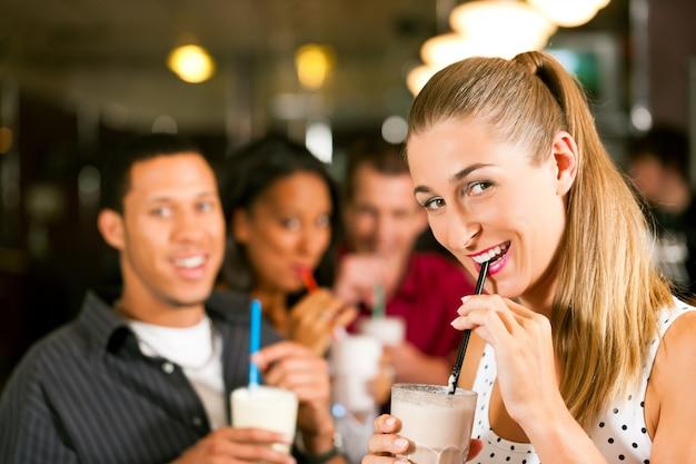 Amis buvant des milkshakes dans un bar