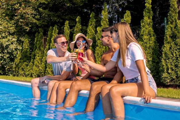 Amis caucasiens buvant des cocktails dans la piscine