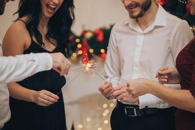 Amis célébrant la fête de noël ou du nouvel an avec des lumières du bengale