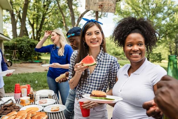 Amis célébrant et mangeant à une fête de hayon