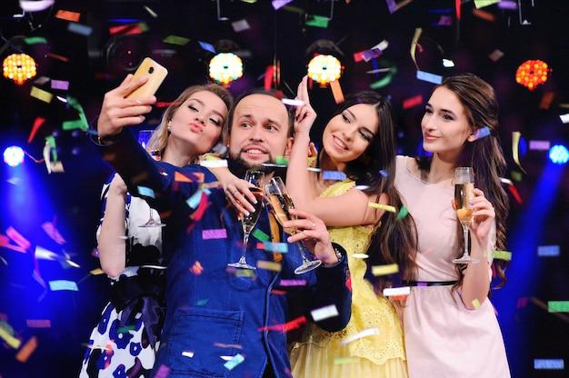 Des amis célèbrent l'événement, rient, dansent et boivent du champagne