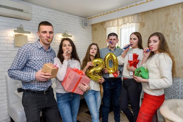 Des amis célèbrent leur anniversaire au café et posent devant la caméra