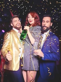 Amis avec champagne appréciant au night club