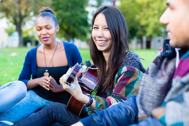 Amis chantant des chansons dans le parc s'amusant ensemble