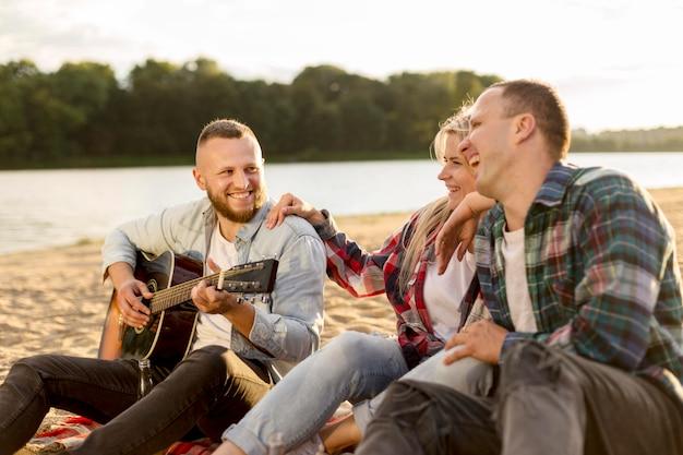 Amis chantant ensemble sur une plage