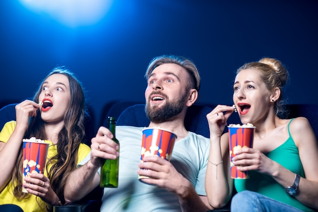 Amis choqués regardant un film assis avec du pop-corn au cinéma