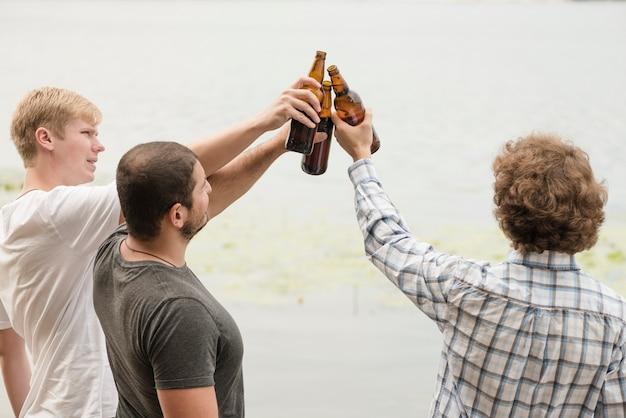 Amis cliquetant des bouteilles près de l'eau