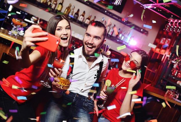 Amis avec des cocktails faisant selfie à la fête