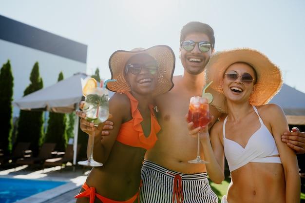 Des amis avec des cocktails posent à la piscine de l'hôtel