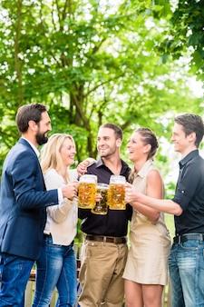 Amis ou collègues sur le jardin de la bière après le travail de grillage avec des boissons