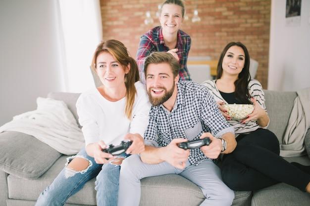 Amis en compétition jouant au jeu vidéo sur la fête