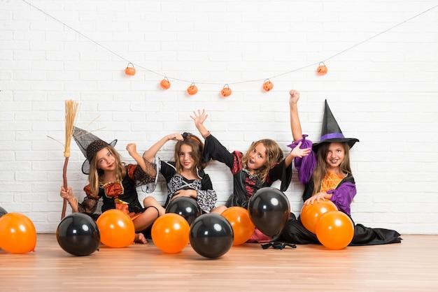 Amis avec des costumes de vampires et de sorcières pour des vacances d'halloween faisant le geste de victoire