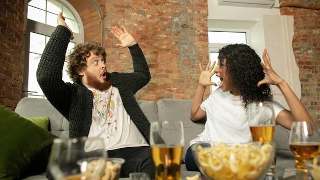 Amis de couples excités regardant le championnat de match de sport à la maison