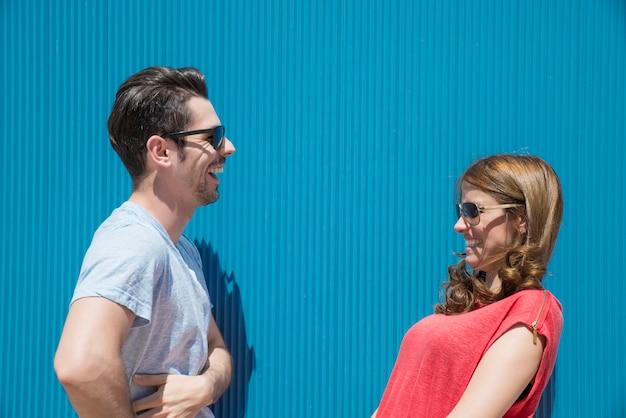 Amis ou couples riant et prenant une conversation contre un mur bleu