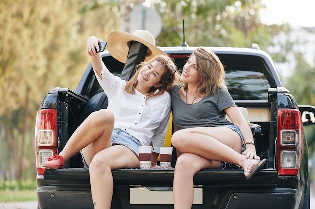 Amis dans le coffre de la voiture prenant selfie