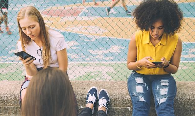 Amis dans le parc à l'aide de smartphones