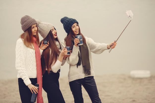 Amis dans un parc d'hiver. filles dans un chapeau tricoté. les femmes avec thermos et thé.