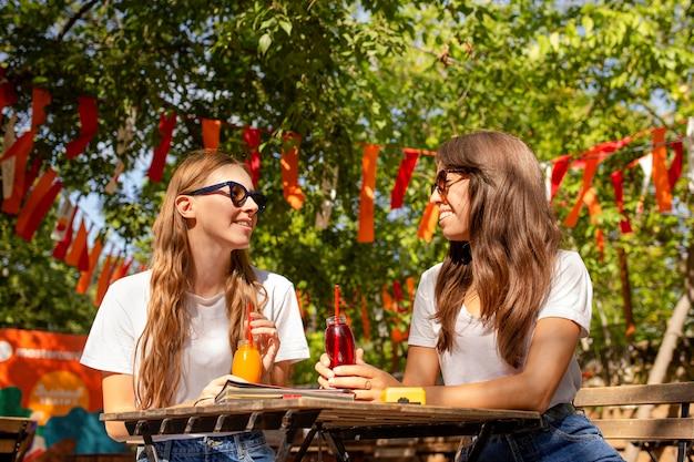 Amis dans le parc tenant des bouteilles de jus de fruits frais