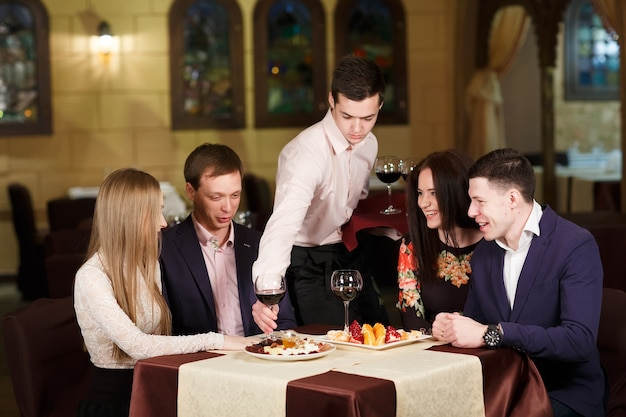 Amis dans un restaurant buvant du vin.