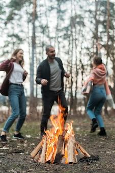 Amis dansant autour du feu de joie