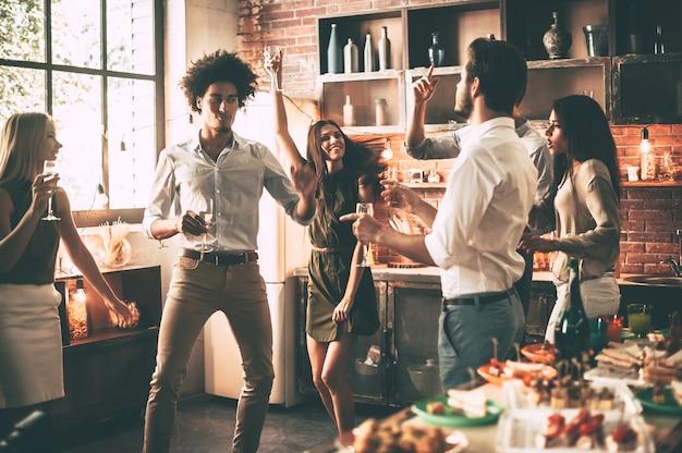 Amis dansant. jeunes joyeux dansant et buvant tout en profitant d'une fête à la maison dans la cuisine