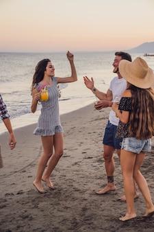 Amis dansant à la plage au coucher du soleil