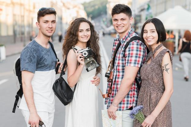 Amis debout sur la rue avec caméra et carte