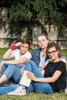Amis décontractés à la mode assis dans le parc