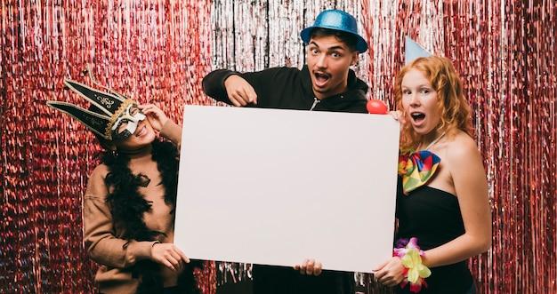 Amis déguisés tenant une feuille de papier vierge