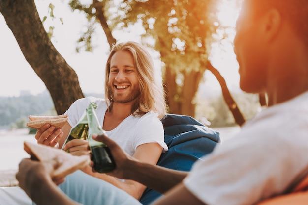 Des amis détendus déjeunent à la nature