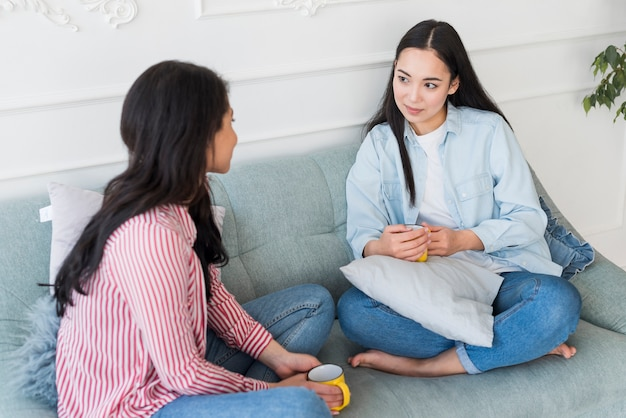 Amis détendus parler assis sur un canapé