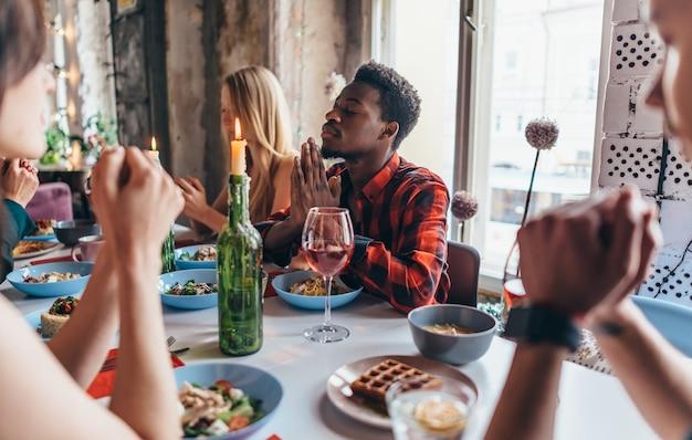 Amis disant la prière avant de manger ensemble.