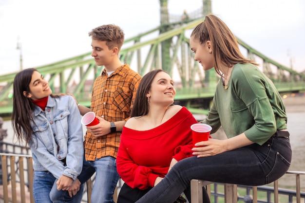 Amis discutant et buvant quelque chose ensemble dans la rue